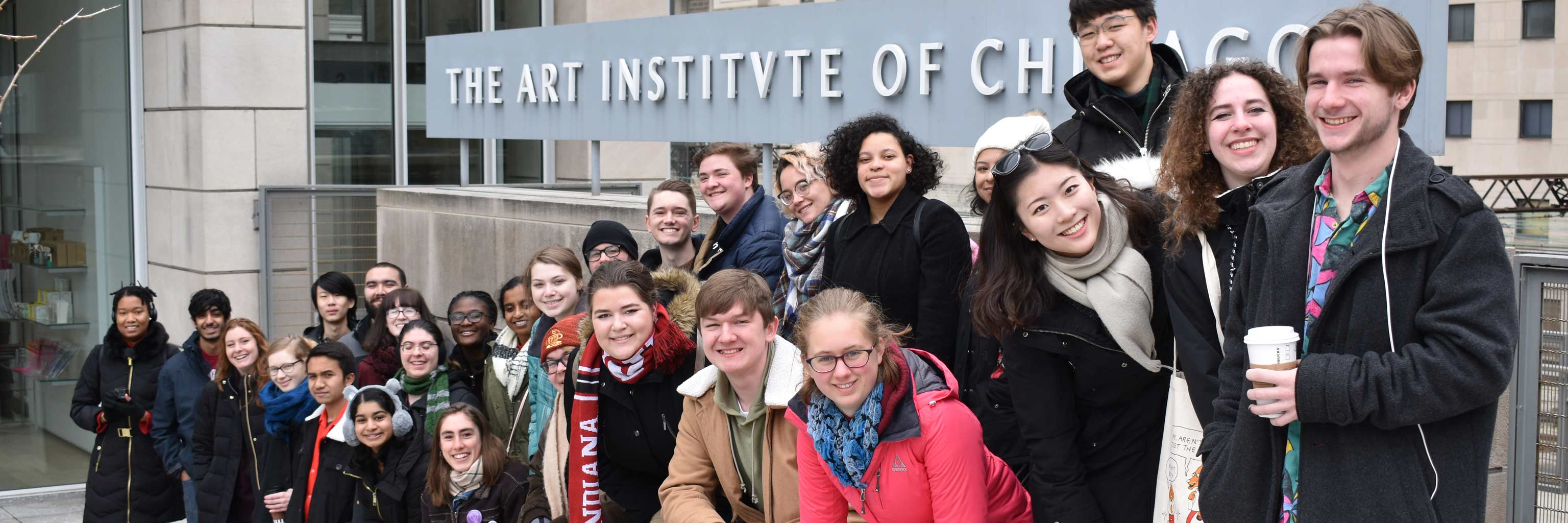 group photo of students in front of art institute sign