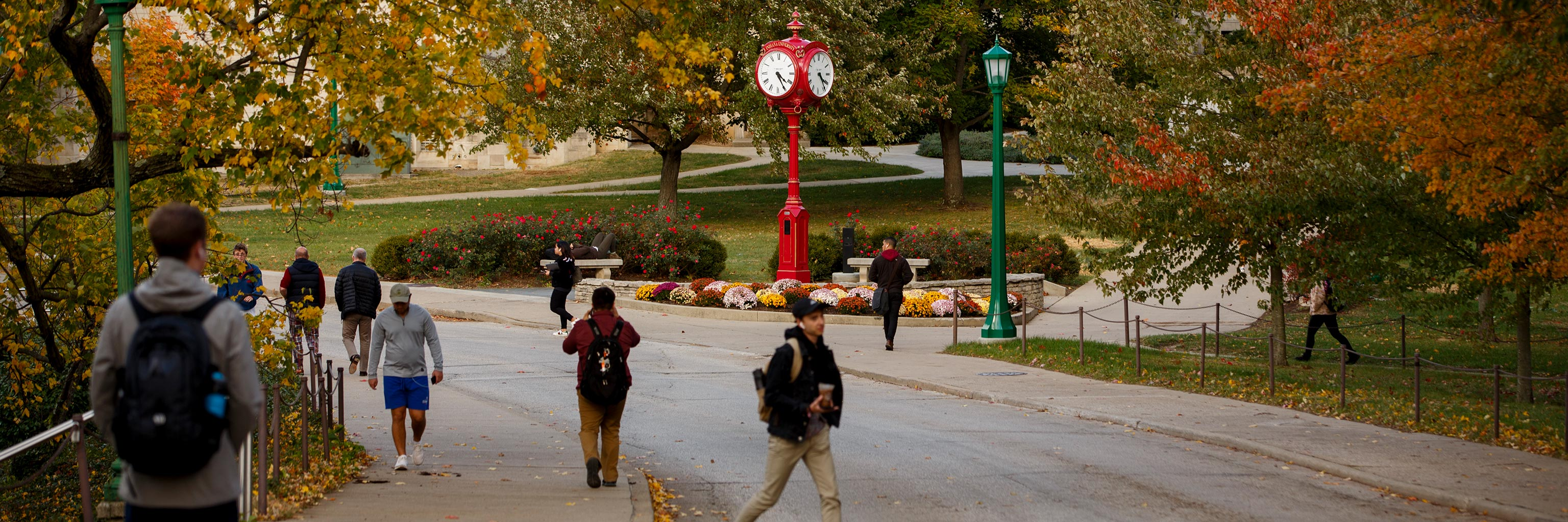 students walking down the autumn weather and side walks on campus