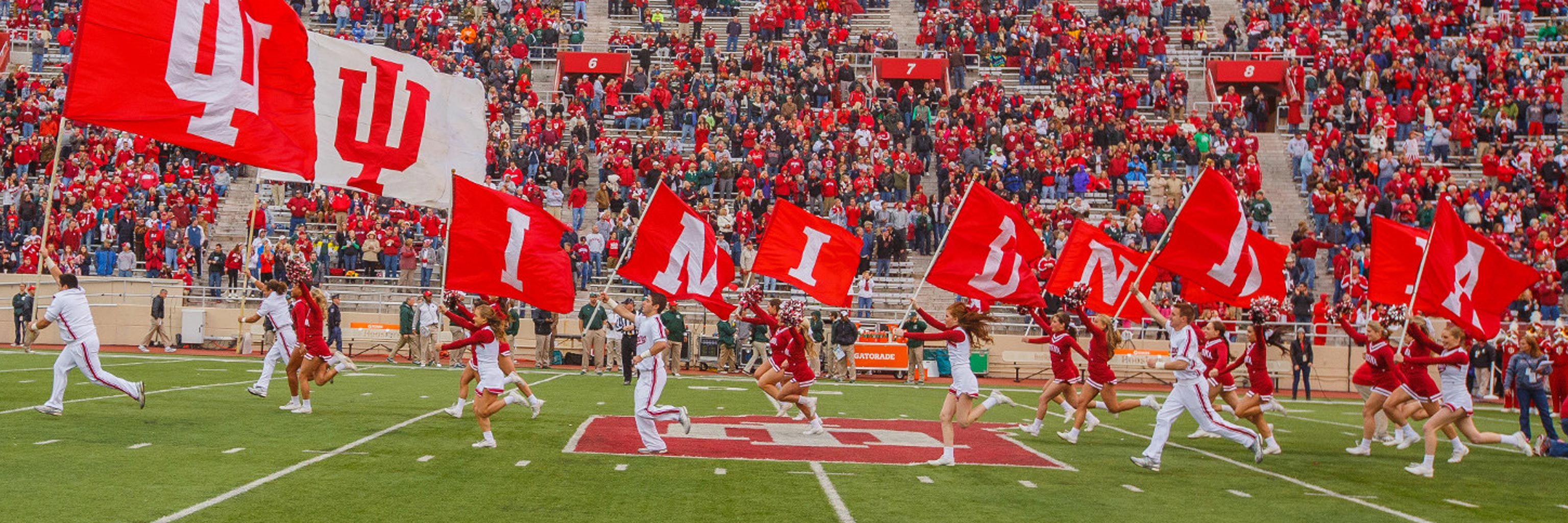 Indiana University cheering team running down football field with school flags