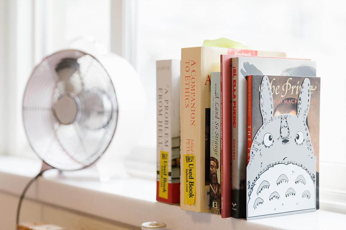 portable fan and books on window ledge