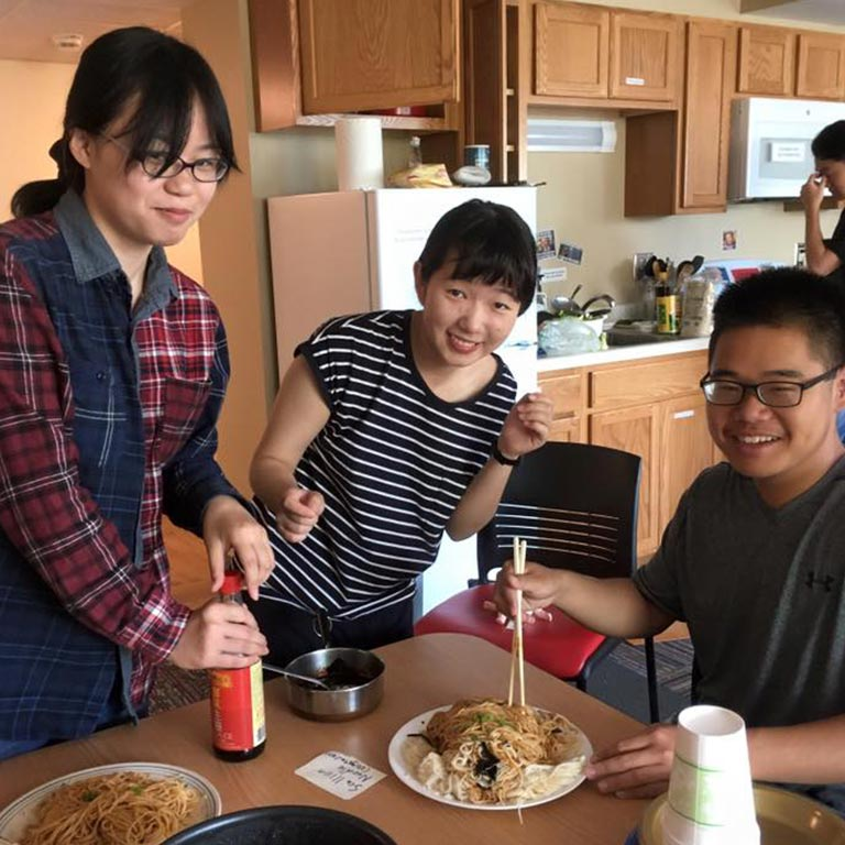 students eating noodles in a kitchen